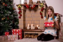 Young girl with gifts sits next to Christmas tree
