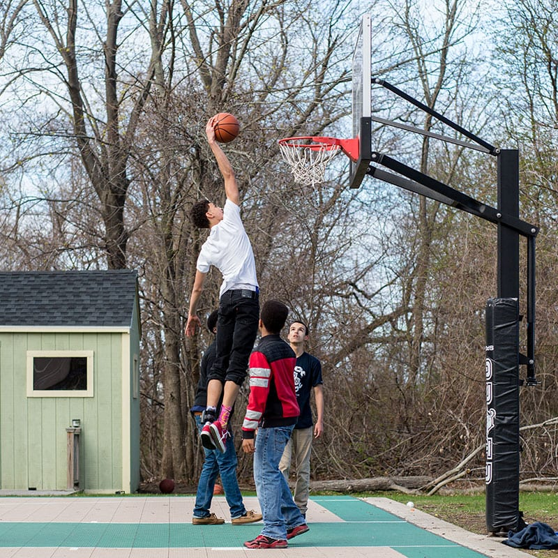 Young man dunks while playing basketball with friends