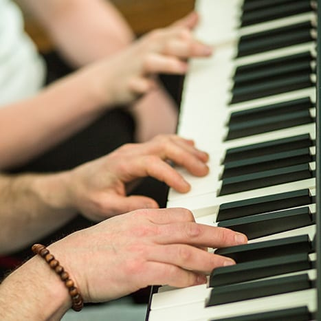 Two young people play piano together