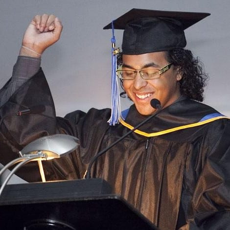 Young man wearing graduation cap and gown smiles while giving speech