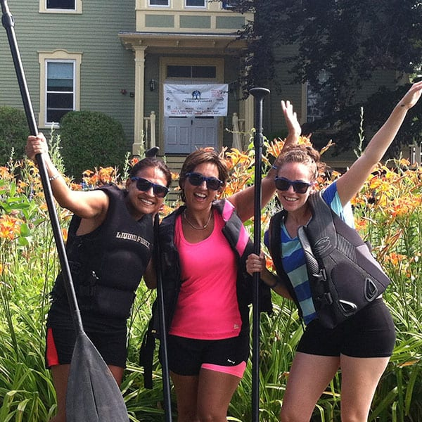 Smiling women wearing lifejackets pose with paddles