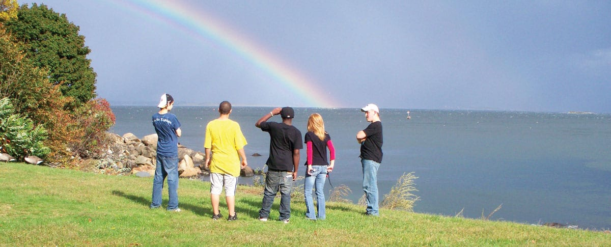 Young people stand near the ocean looking at a rainbow in the sky