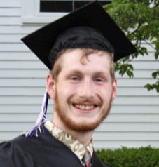 Young man smiles while wearing graduation cap and gown
