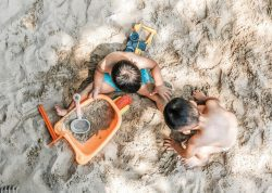 Two children on the beach playing in the sand.